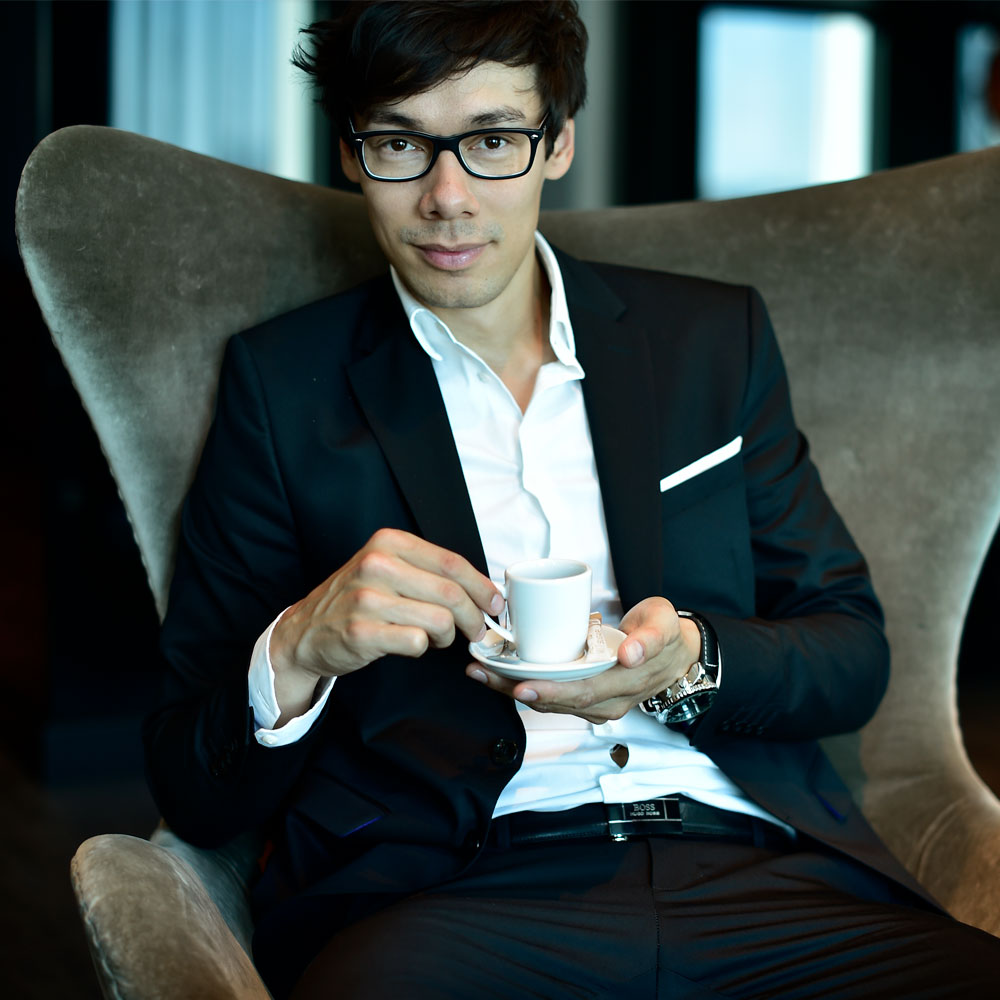 Florian Clyder mit Tasse in der Hand auf einem Sessel